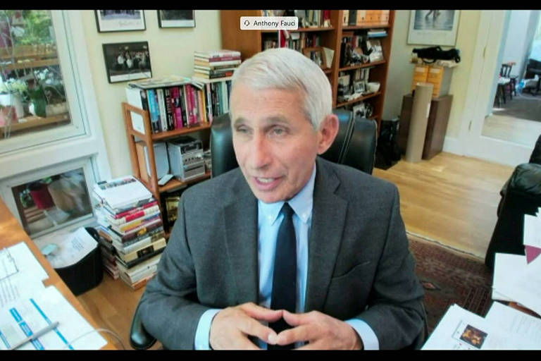 Anthony Fauci aparece em um frame de vídeo em uma sala com sofá preto e estante de livros