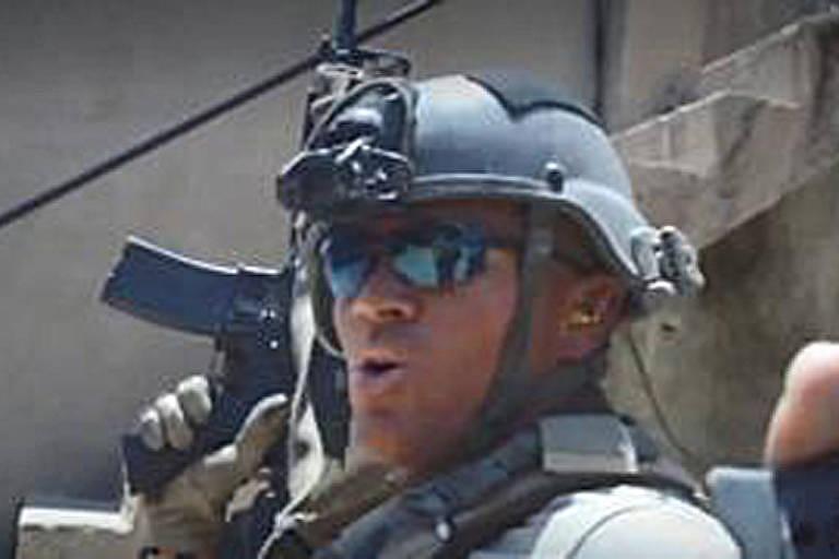 foto do rosto de um homem branco com óculos, capacete e metralhadora
