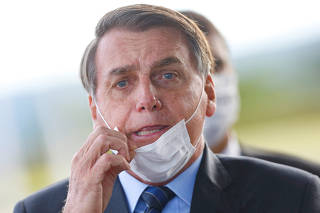 Brazil's President Jair Bolsonaro adjusts his mask as he leaves Alvorada Palace, amid the coronavirus disease (COVID-19) outbreak in Brasilia