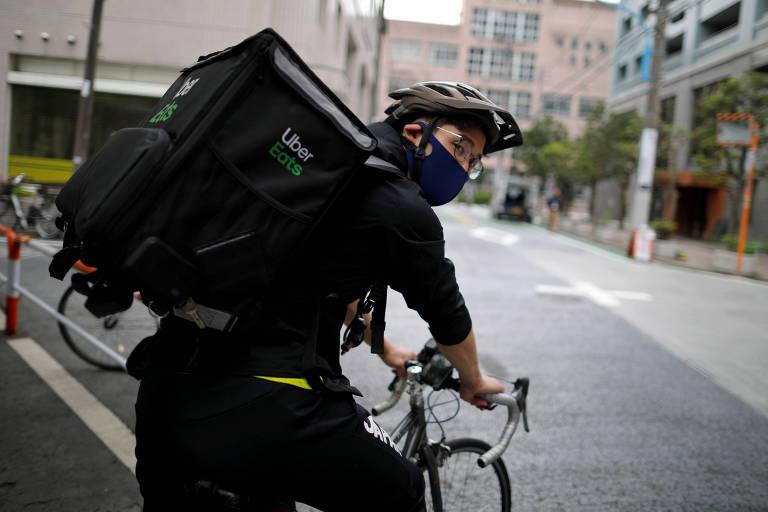 Um ciclista entregador de delivery com a mochila da Uber Eats nas costas