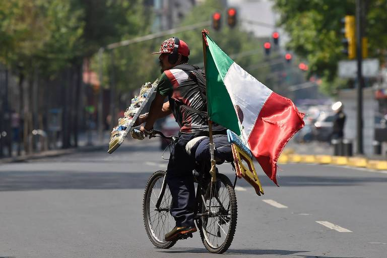 Vendedor carrega bandeira mexicana em rua da Cidade do México