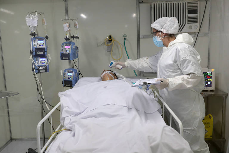 Enfermeira usa máscara, óculos e macacão de proteção e mede temperatura com termômetro de infravermelho; paciente está deitado na cama e há equipamentos pelo quarto