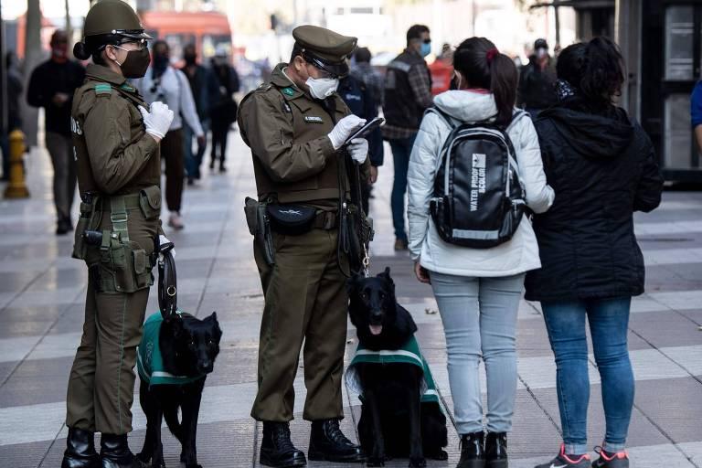 Policiais param duas pessoas na Plaza de Armas, em Santiago, após o governo chileno decretar 'lockdown'