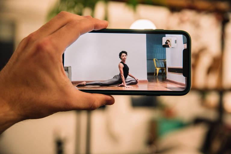 Mariana do Rosário, bailarina do Grupo Corpo, que oferecerá aulas online; vemos a imagem da bailarina,  que usa um body preto e uma calça cinza, alongando-se no chão de sua casa; mas a vemos através de uma tela de celular na mão do fotógrafo, pois a imagem foi feita por videoconferência