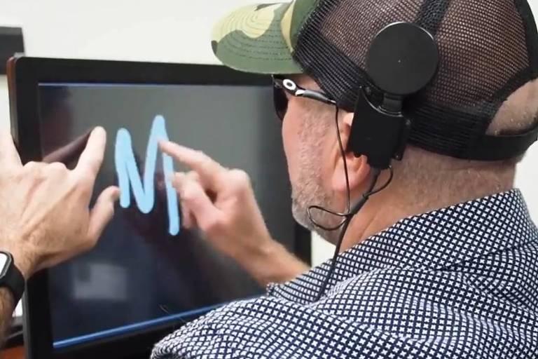 Homem cego faz o desenho da letra M com o dedo em uma tela que está em sua frente