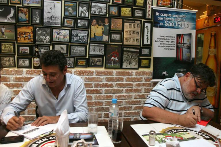 """Com o ex-zagueiro Dario Pereyra, o jornalista Luís Augusto """"Menon"""" Símon (a dir) autografa o seu livro Tricolor Celeste, que narra a trajetória de sucesso de jogadores uruguaios no Tricolor"""