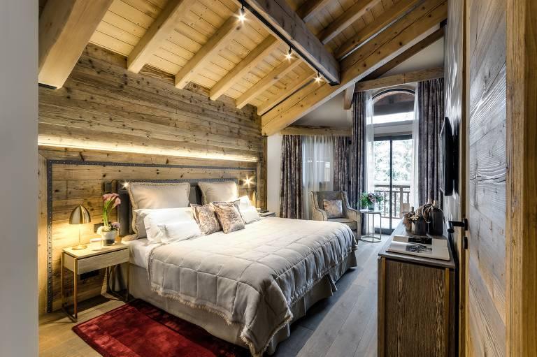 Quarto com madeira no teto, piso e paredes, telhado inclinado e cama de casal