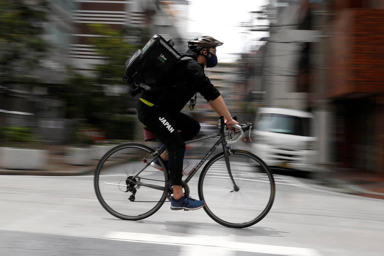 O esgrimista japonês Ryo Miyake, medalha de prata na Olimpíada de Londres-2012, faz entregas de comida usando uma bicicleta da Uber em Tóquio durante a pandemia de Covid-19