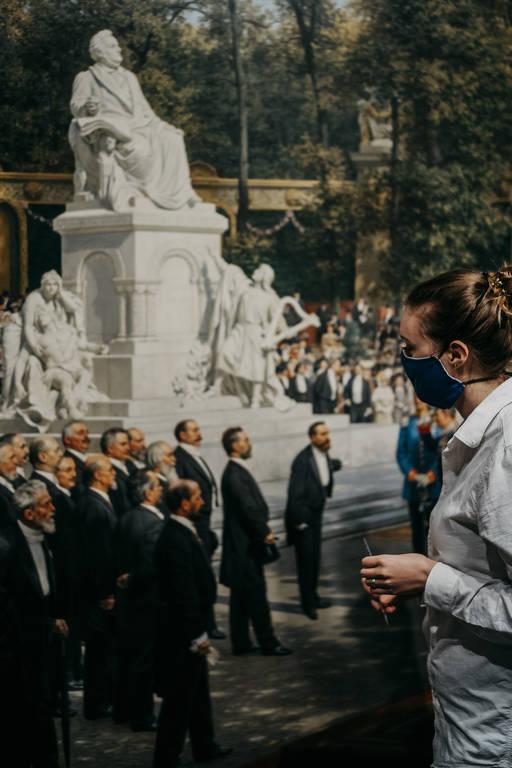 Mulher vestindo máscara observa quadro