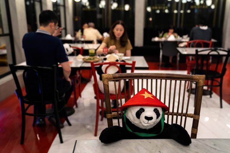 Pequeno panda de pelúcia com chapéu triangular vermelho sentado à mesa do restaurante