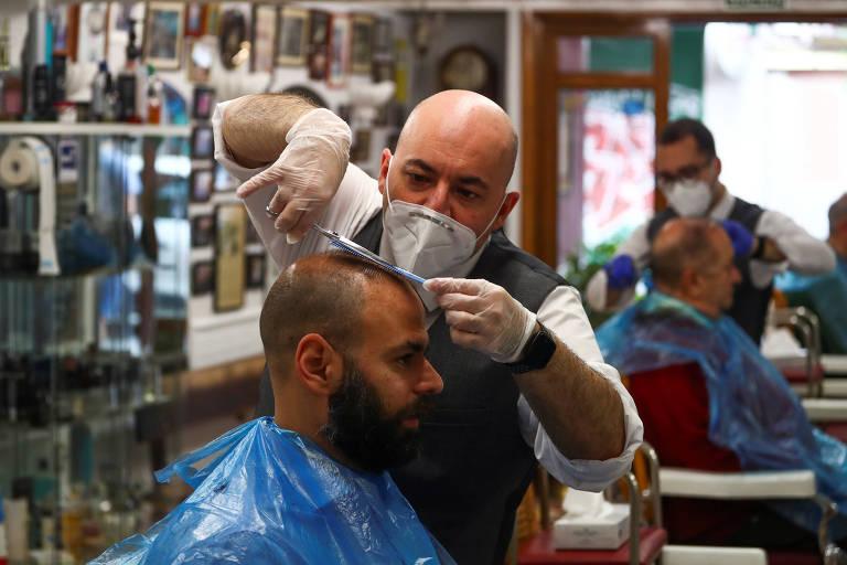 Cabeleireiro com máscara e luvas corta cabelo de cliente em Madri
