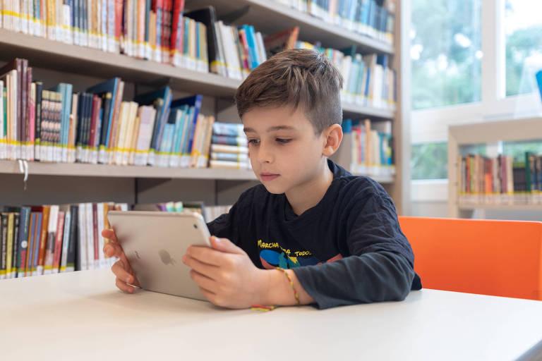 Menino lê em um tablet dentro de uma biblioteca escolar