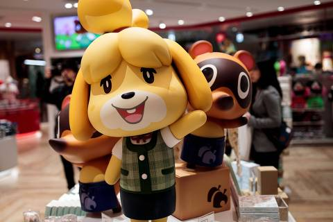 This picture taken on November 19, 2019 shows dolls of Nintendo game characters Isabelle (C), known as Shizue in Japan, and Tom Nook (R), known in Japan as Tanukichi, from the Animal Crossing series of video games as they are displayed at a new Nintendo store during a press preview in Tokyo. - The leisurely world of Nintendo's latest release