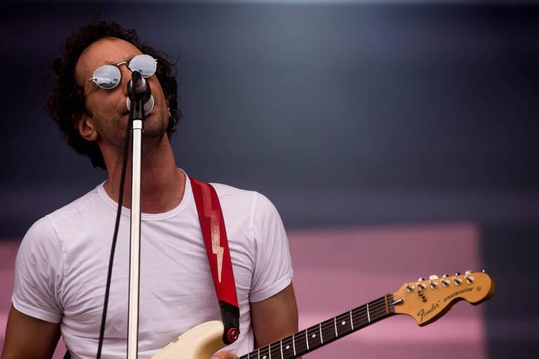 homem de camiseta branca e óculos escuros cantando em frente a um microfone e empunhando uma guitarra