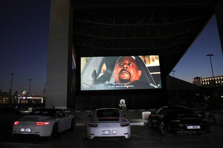 Pessoas de máscara e em carros de luxo aproveitam evento de pré-inauguração de cinema drive-in em Dubai; estrutura foi criada para driblar fechamentos dos cinemas devido à pandemia