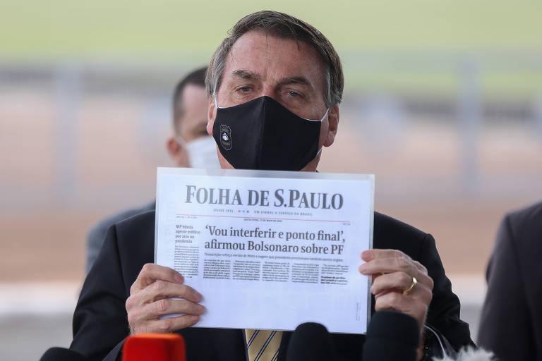 O presidente Jair Bolsonaro mostra cópia da Primeira Página da Folha ao falar com jornalistas em frente ao Palácio da Alvorada na manhã desta sexta-feira; ele criticou a cobertura da imprensa