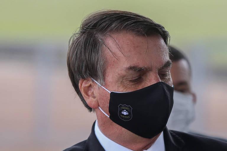O presidente Jair Bolsonaro usa máscara em homenagem a policiais federais, durante entrevista em frente ao Palácio da Alvorada