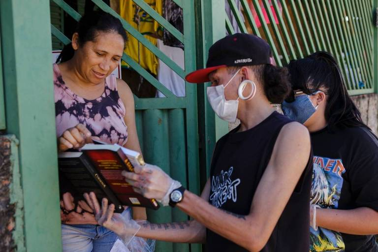 Voluntários entregam livros em distribuição de cestas básicas em Recanto das Emas, periferia do Distrito Federal