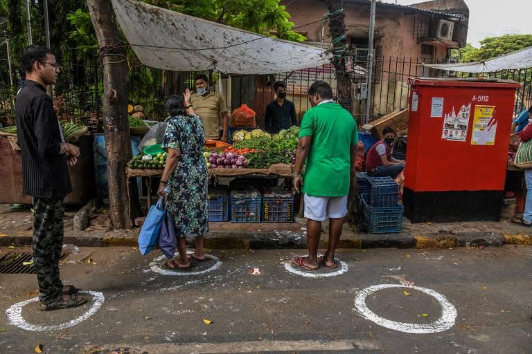 Marcações pintadas no chão indicam o distanciamento social ideal em feira de rua em Mumbai