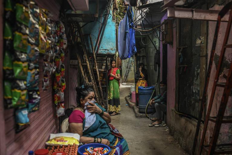 Moradores em uma viela estreita na favela de Dharavi, em Mumbai
