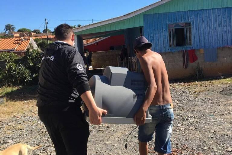Funcionário do Núcleo Regional de Educação do Paraná leva televisão para família pobre com 3 crianças poder acompanhar aulas na cidade de Rebouças; à dir., um dos filhos ajuda a levar o equipamento
