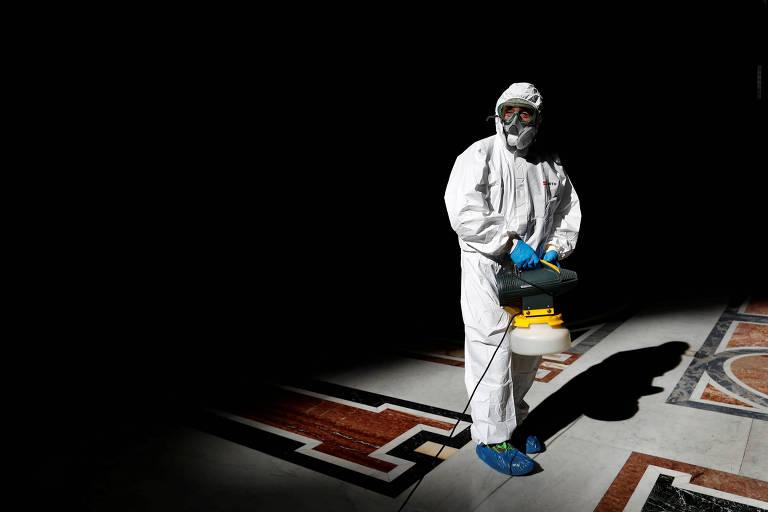Funcionário com trajes brancos, máscara e óculos para proteção contra vírus desinfeta chão de mármore da basílica