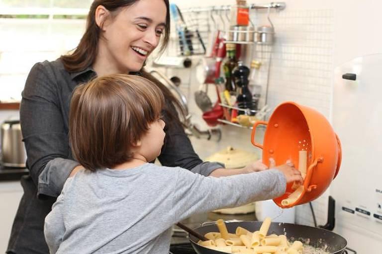 Criança em banco de madeira, na frente do fogão, ajuda mãe a preparar macarronada