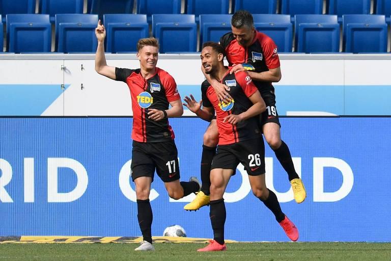 Ibisevic pula nas costas do brasileiro Matheus Cunha após ele fazer gol pelo Hertha Berlin