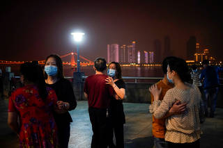 People wearing protective face masks dance under the Yangtze River Bridge in Wuhan