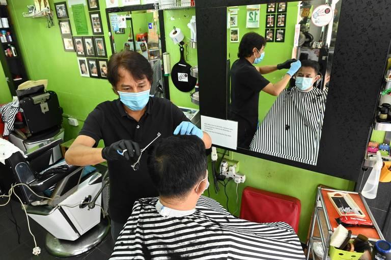 Homem corta o cabelo em barbearia em Singapura, depois que  governo aliviou as medidas de isolamento social e permitiu a reabertura desses estabelecimentos