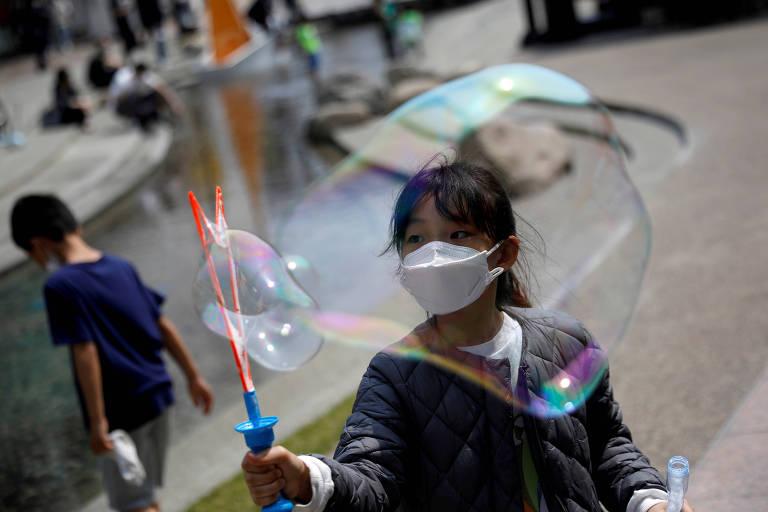 Garota com máscara brinca com bolhas de sabão em shopping em Gimpo, na Coreia do Sul