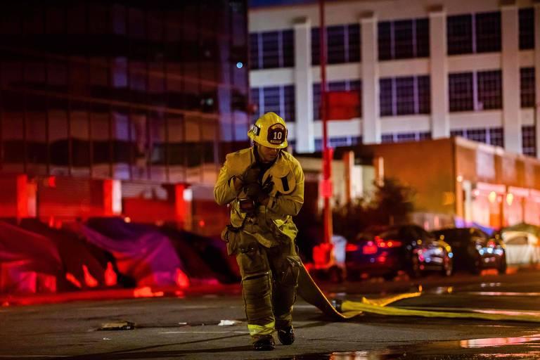 Bombeiro carrega mangueira após incêndio ocorrer em prédio comercial no centro de Los Angeles