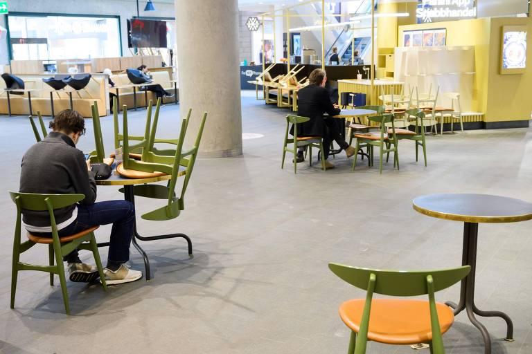 pessoas sentadas sozinhas em mesas de área de alimentação, com muito espaço entre cada mesa