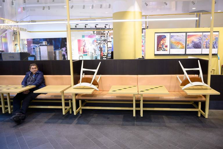 Homem sentado em mesa de lanchonete, com cadeiras colocadas sobre outros locais nos bancos para evitar que pessoas se sentem
