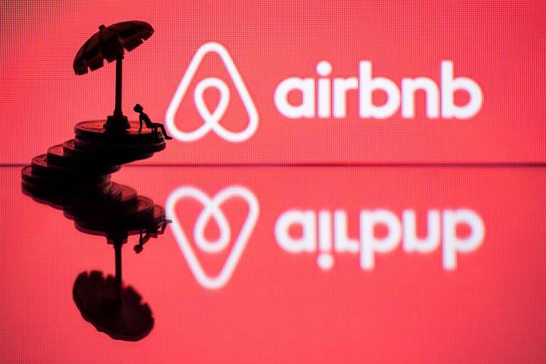 Na foto, uma montagem em cima de uma mesa de vidro, na qual ao fundo aparece o logo do Airbnb em vermelho e, mais à frente, aparece um brinquedo em formado de um homem sentado embaixo de um guarda-sol