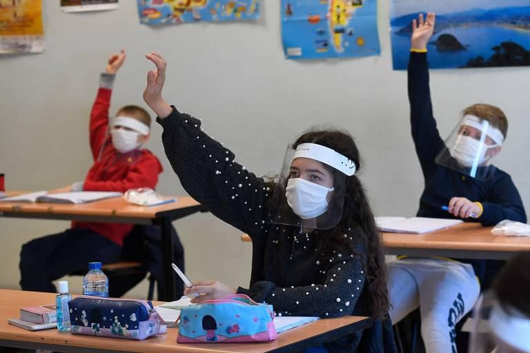 foto de três crianças, uma menina, à frente, e dois meninos, atrás, setnado em carteiras de uma sala de aula e com o braço levantado