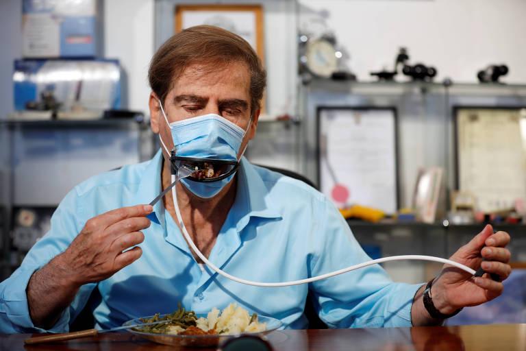 Meir Gitelis come enquanto usa máscara equipada com boca mecânica