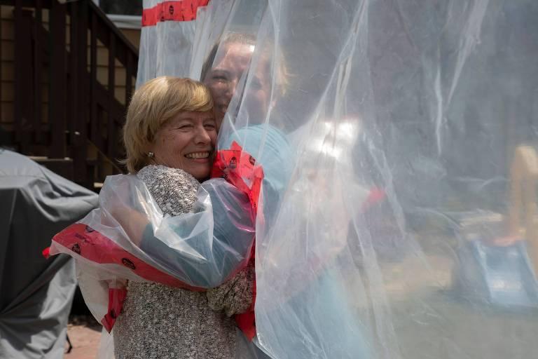Carolyn Ellis, à dir., abraça a mãe, Susan Watts, por meio da 'luva do abraço' em Guelph, no Canadá