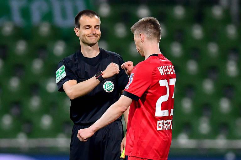 Árbitro e Mitchell Weiser, do Bayer Leverkusen, tocam os punhos após jogo da Bundesliga