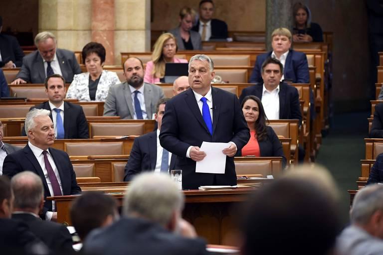 foto de orbán em pé, de terno e segurando um papel, em meio à vários parlamentares sentado em mesas da casa