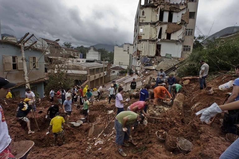 Bombeiros e voluntários fazem buscas nos escombros em Nova Friburgo; esperança de achar sobreviventes é praticamente nula. A chuva causou deslizamentos em toda a região serrana do Rio de Janeiro, deixando centenas de mortos, em janeiro de 2011.