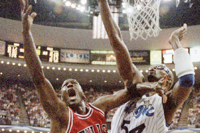 Jordan salta para a bandeja, e Grant, já no Orlando Magic, tenta bloquear o astro do Chicago Bulls