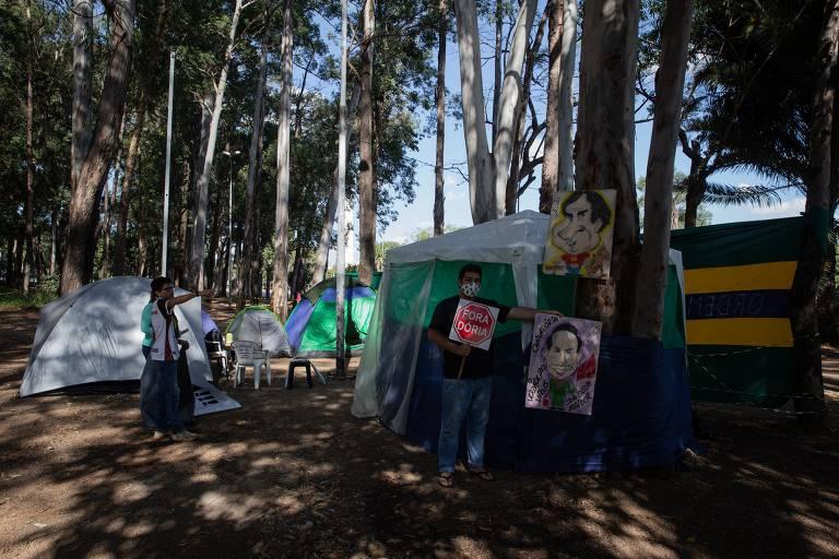 """Homem segura placa com o dizer """"Fora, Doria"""" em foto de 20 de maio que mostra acampamento de bolsonaristas próximo a Assembleia Legislativa de São Paulo; grupo defendia a automedicação com hidroxicloroquina, azitromicina e ivermectina contra a Covid-19"""
