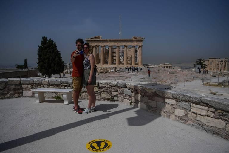 Casal tira selfie com construção antiga, de colunas, ao fundo