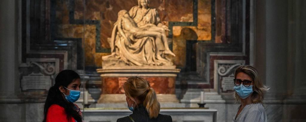 Três mulheres com máscara na frente de estátua
