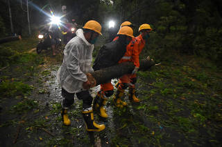 Members of National Disaster Rescue Force remove a branch of an uprooted tree after Cyclone Amphan made its landfall, in Digarh