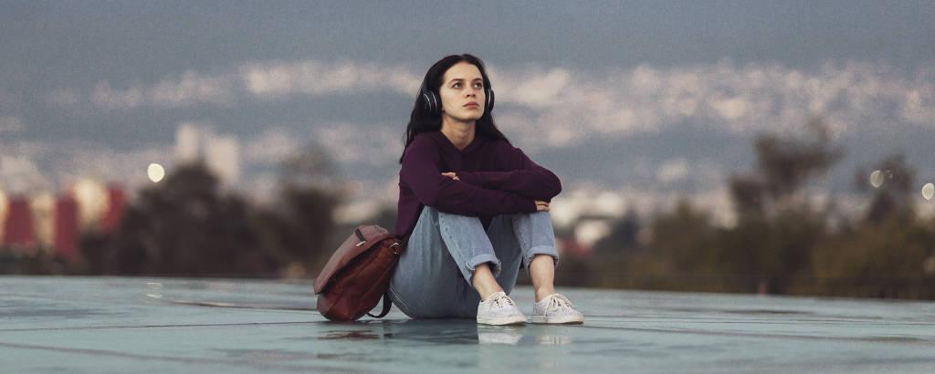menina sentada em vidro ouvindo música contra paisagem montanhosa
