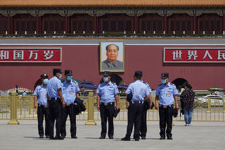Police officers stand on Tiananmen Square in Beijing