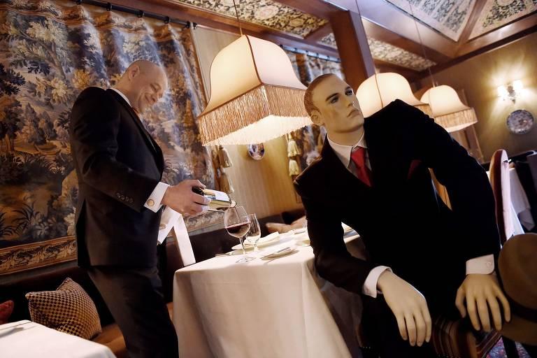 Homem com terno elegante serve vinho para manequim que usa  terno antigo e gravata cor de vinho
