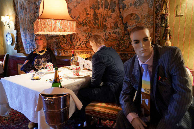 Um manequim com terno cinza e gravata colorida olha fixamente para frente. Atrás dele,  um casal de manequins está à mesa